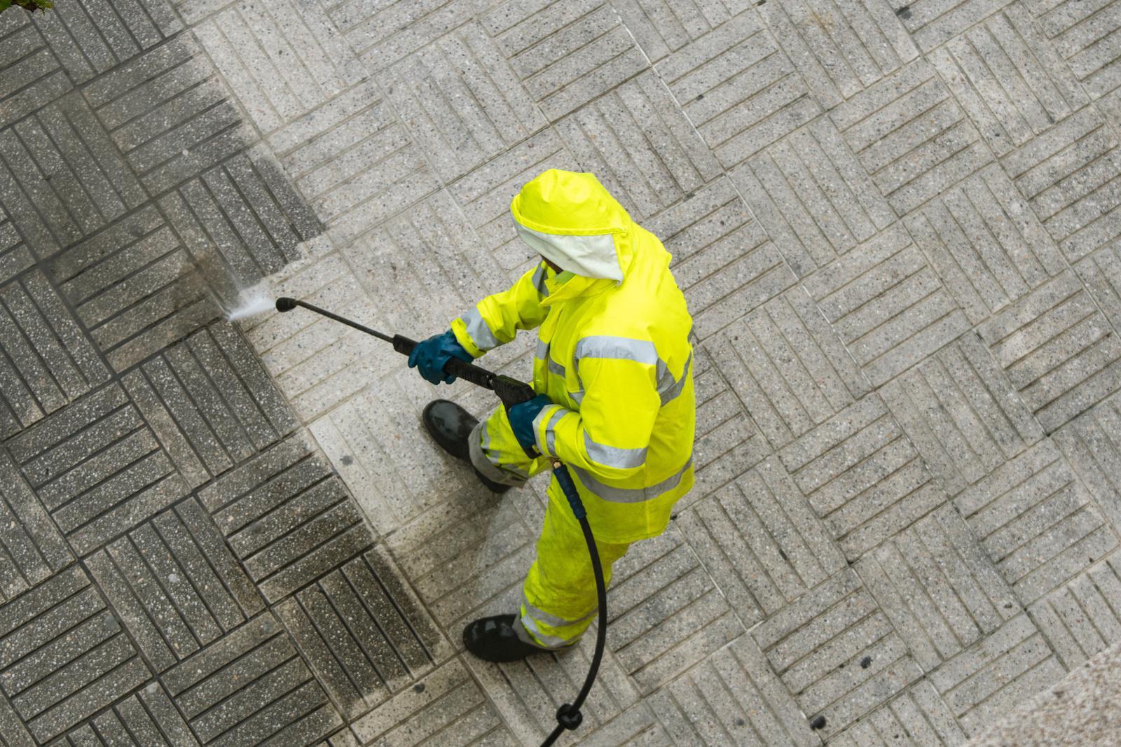 下雨天,一名工人正在用高压水枪清洗街道人行道